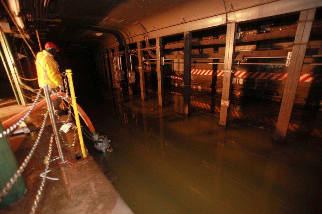 Nhân viên bảo trì hệ thống tàu điện ngầm New York bơm thoát nước ngập do bão Sandy vào năm 2012. Ảnh: New York Times.