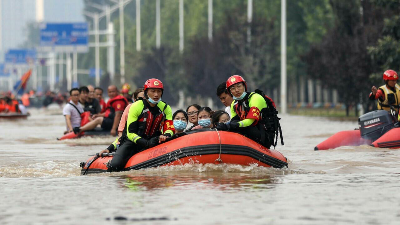 Nhân viên cứu hộ sơ tán người dân khỏi vùng ngập ở Trịnh Châu vào ngày 22/7. Ảnh: AFP.