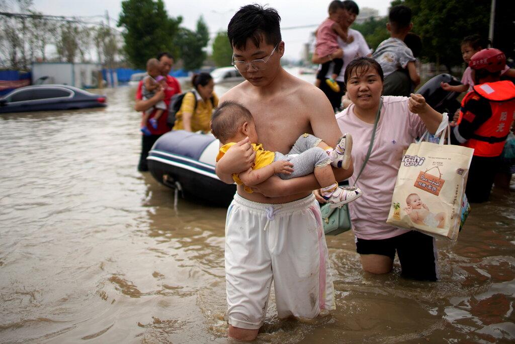 Người dân Trịnh Châu lội qua vùng ngập vào ngày 22/7, được lực lượng cứu hộ hướng dẫn đến nơi an toàn. Ảnh: Reuters.