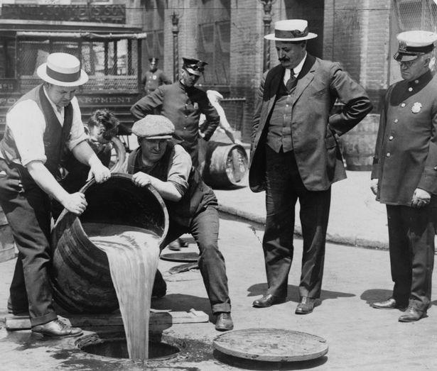 Nhà chức trách đổ bỏ những thùng bia lậu trên đường phố New York trong thời gian lệnh cấm rượu bia có hiệu lực, khoảng 1920- 1933. Ảnh: Mirror
