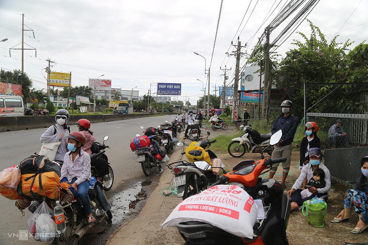 Xe máy lỉnh kỉnh đồ đạc đậu gần chốt kiểm soát từ TP HCM vào Long An, sáng 25/7. Ảnh: Đình Văn