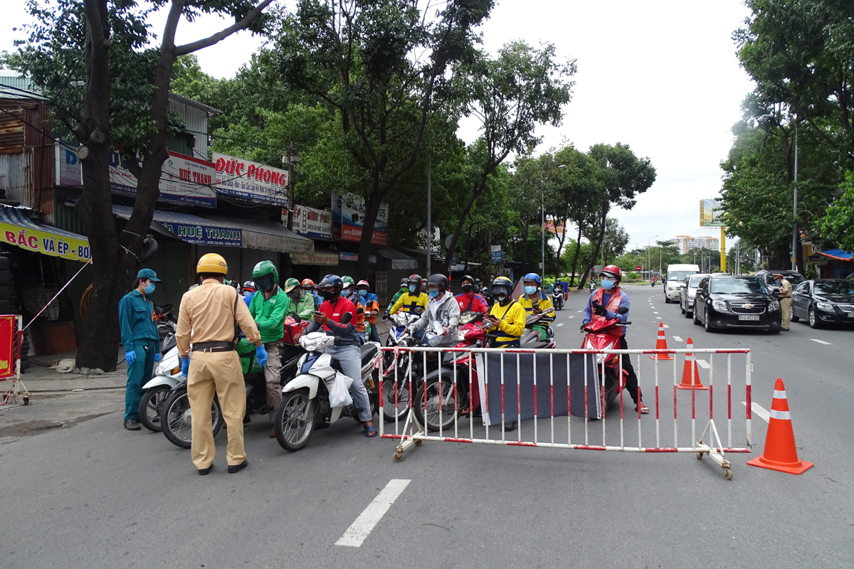 Nhiều shipper chờ kiểm tra giấy tờ qua chốt kiểm soát đường Đinh Bộ Lĩnh, quận Bình Thạnh, chiều 25/7. Ảnh: Hà An.