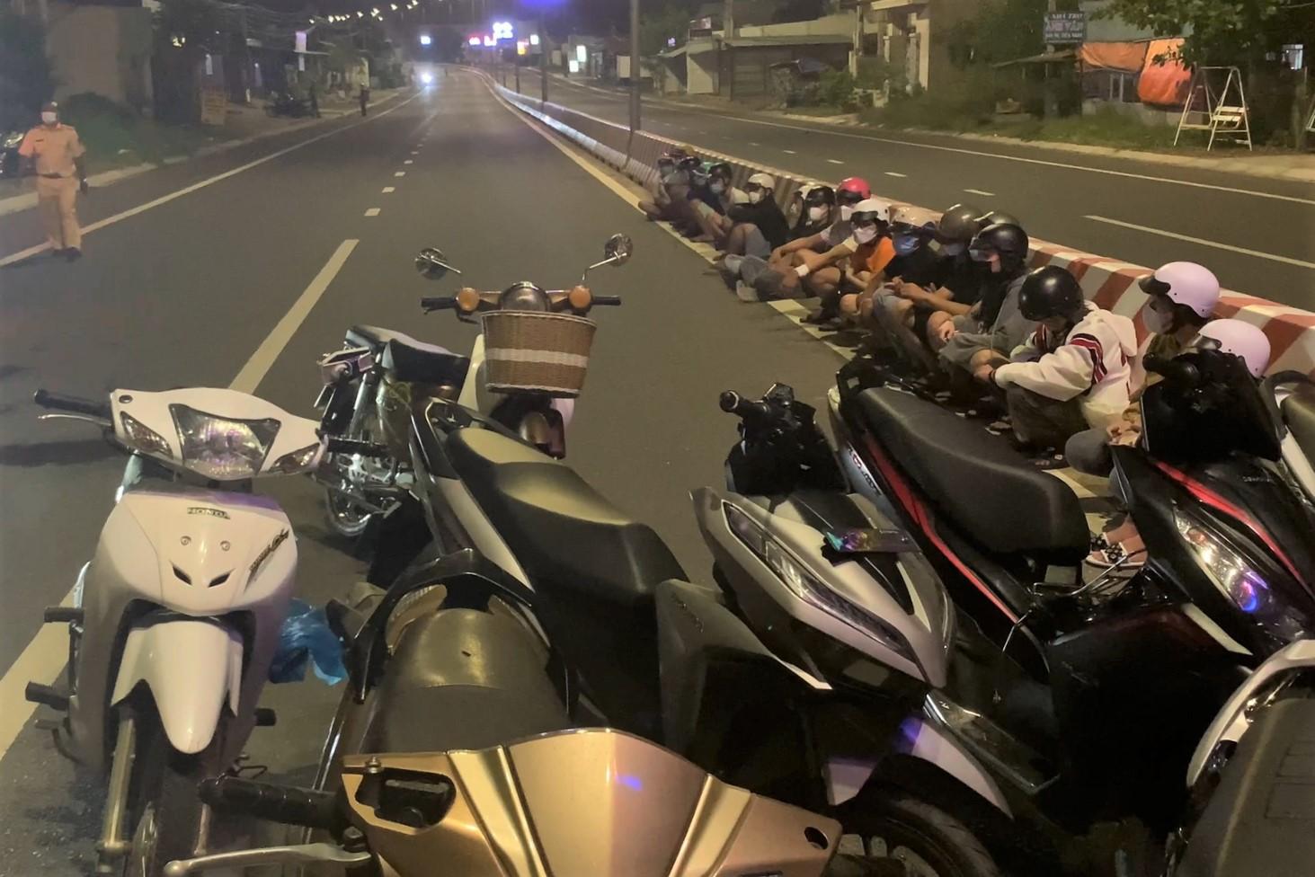 Các quái xế và một số phương tiện bị bắt giữ trên đường Võ Nguyên Giáp, sáng 25/7. Ảnh: Công an cung cấp.
