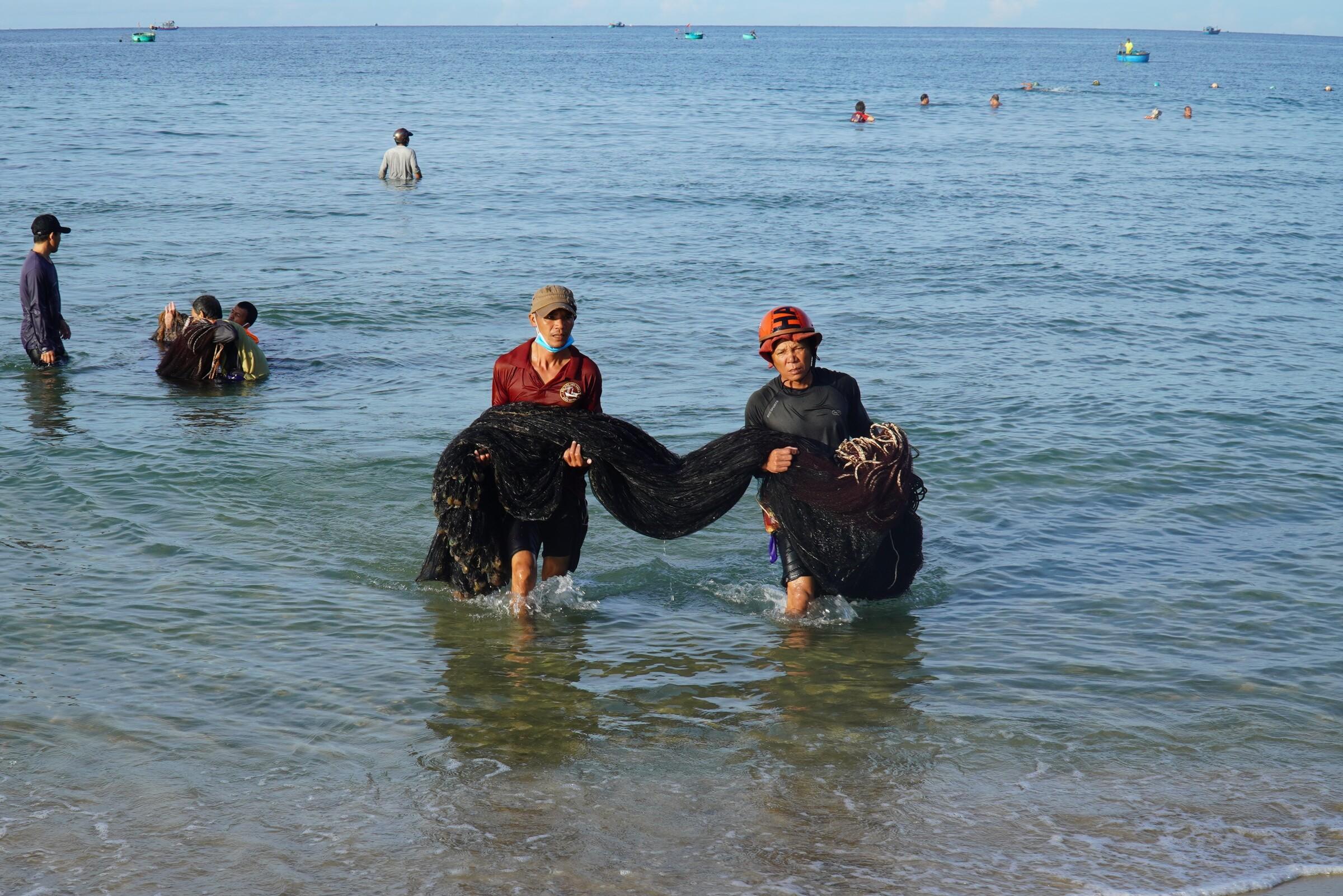 Ông Bùi Đức Minh (bên phải) cùng đồng nghiệp khiêng lưới ruốc lên bờ sau mẻ đánh. Ảnh: Việt Quốc.