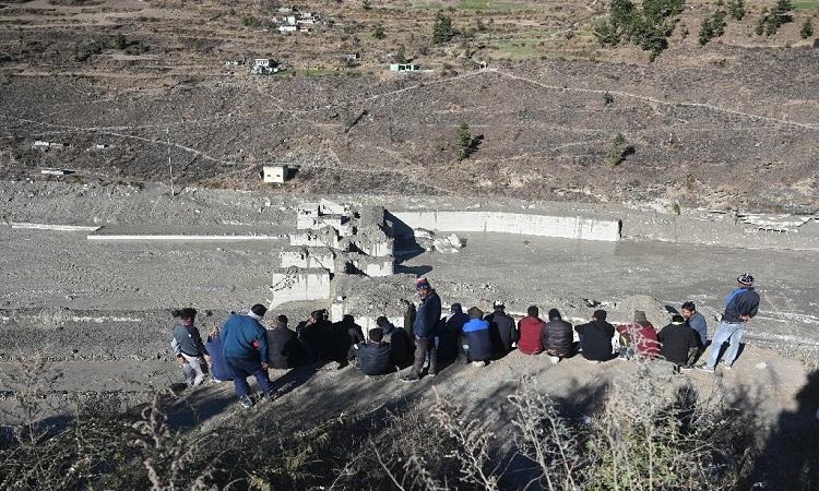 Người dân nhìn xuống đống đổ nát của đập Tapovan bị lũ quét cuốn trôi trên dãy Himalaya. Ảnh: Phys.org.
