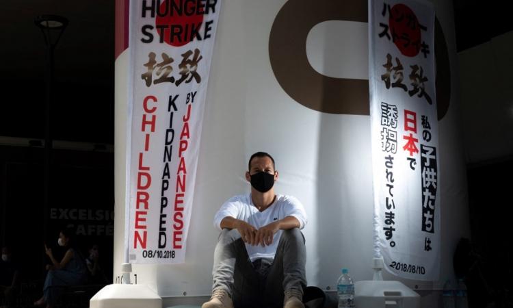 Vincent Fichot tuyệt thực ngồi bên ngoài một ga tàu ở Tokyo, Nhật Bản, hôm 10/7. Ảnh: AFP.