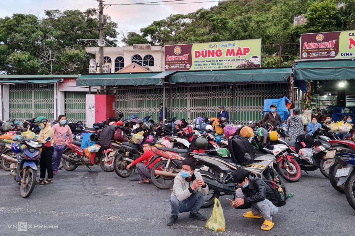 Người dân ngồi chờ đợi trên đèo Hải Vân chờ CSGT dẫn đường. Ảnh: Vạn An