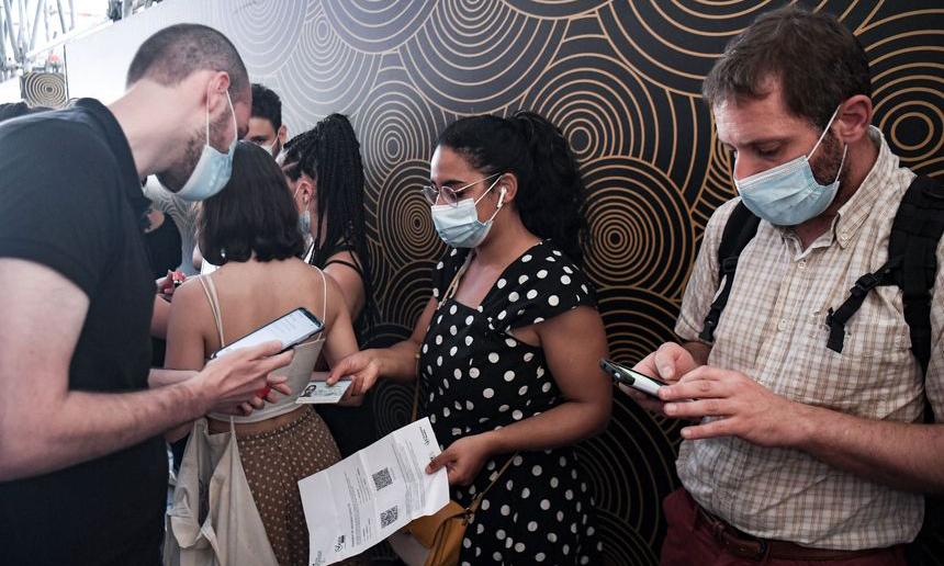 Người dân xuất trình giấy chứng nhận y tế trước khi vào một rạp chiếu phim ở Paris, Pháp, hôm 21/7. Ảnh: AFP.