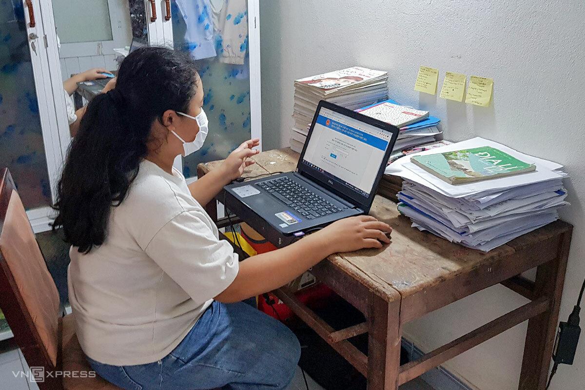 Dang mượn máy tính của chị để kiểm tra lại điểm thi tốt nghiệp THPT. Ảnh: Thành Linh.