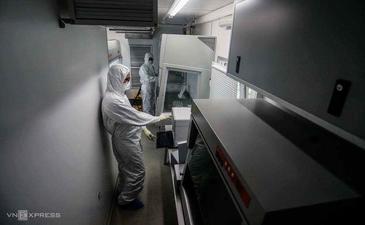 Nhân viên Trung tâm Nhiệt đới Việt - Nga (trực thuộc Bộ Quốc phòng) trùm kín đồ bảo hộ và đứng trong labo tiến hành xét nghệm Covid-19, tại TP Hồ Chí Minh. Ảnh: Hữu Khoa