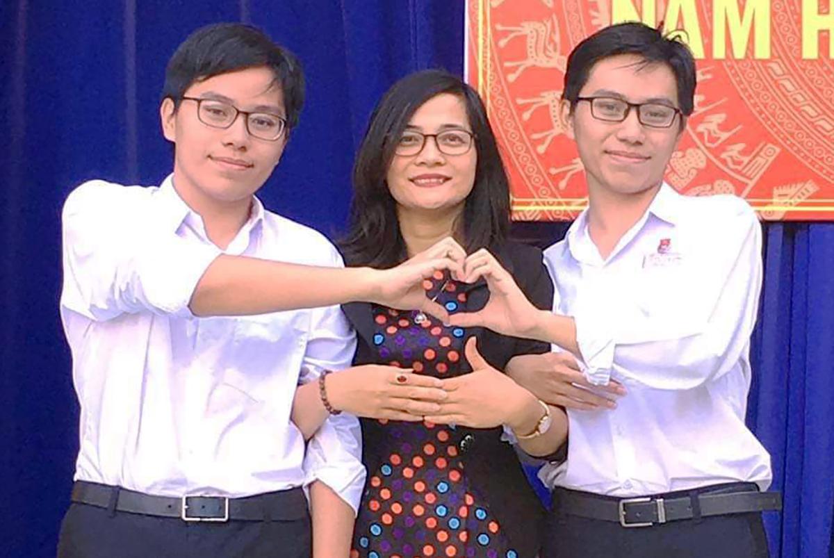Anh em sinh đôi Quốc Bảo (bên trái) và Hữu Bảo chụp hình cùng cô giáo. Ảnh: Nhân vật cung cấp.