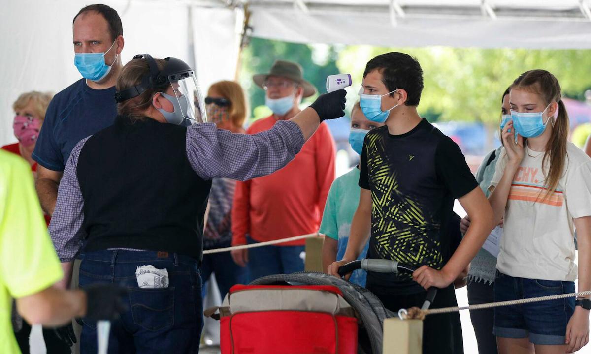 Người dân Mỹ được kiểm tra thân nhiệt trước khi vào công viên ở thành phố Branson, bang Missouri hôm 13/7. Ảnh: AP.