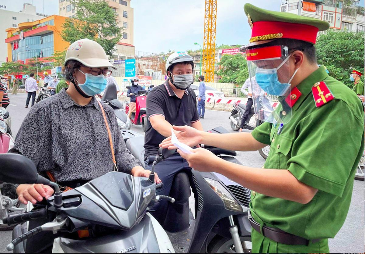 Lực lượng công an kiểm tra việc việc chấp hành của người dân với Chỉ thị 17 tại phố Phạm Ngọc Thạch, chiều 28/7. Ảnh: Giang Huy.