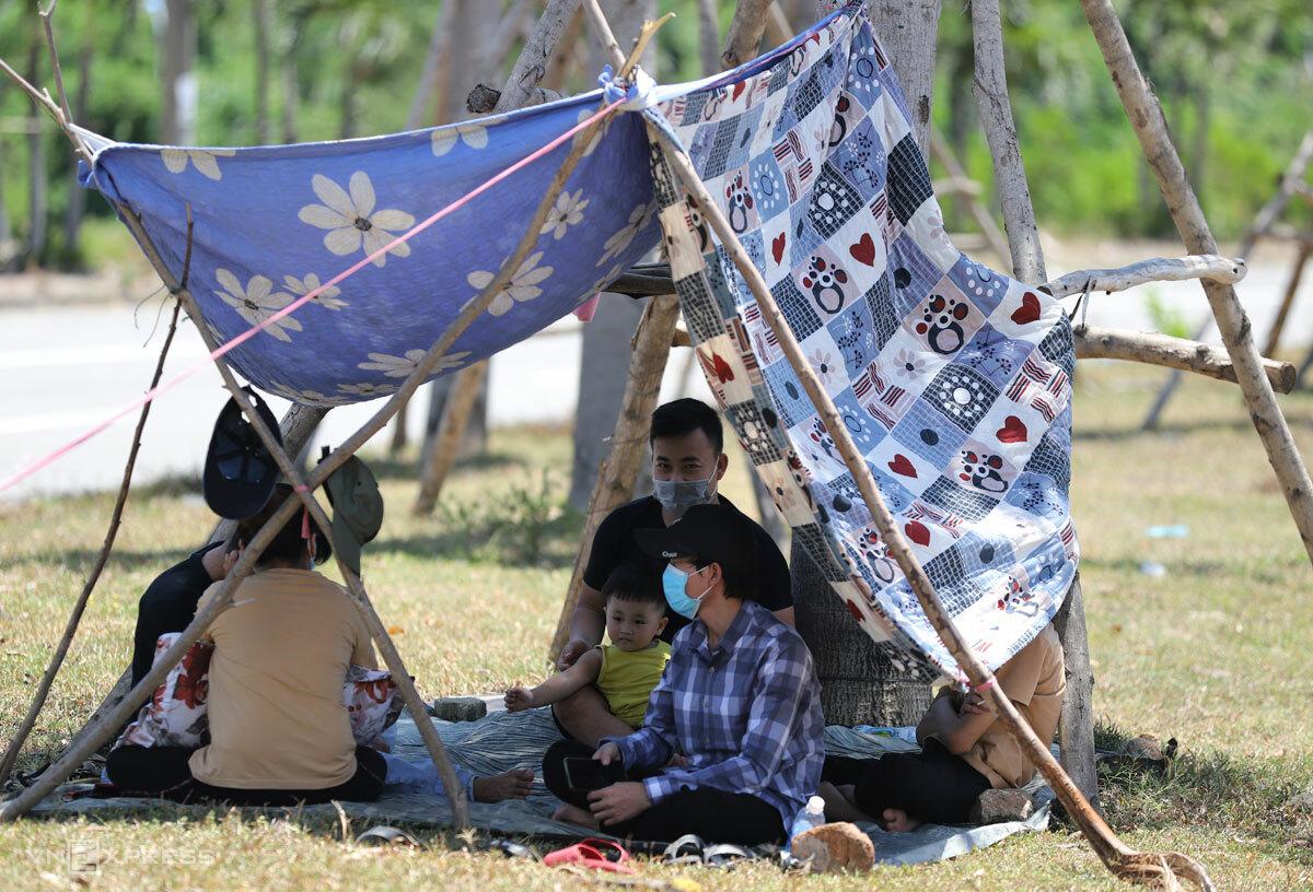 Một gia đình có con nhỏ trở về từ TP HCM ngồi nghỉ trong lều tạm ở chốt kiểm dịch ở Lăng Cô, Huế. Ảnh: Võ Thạnh