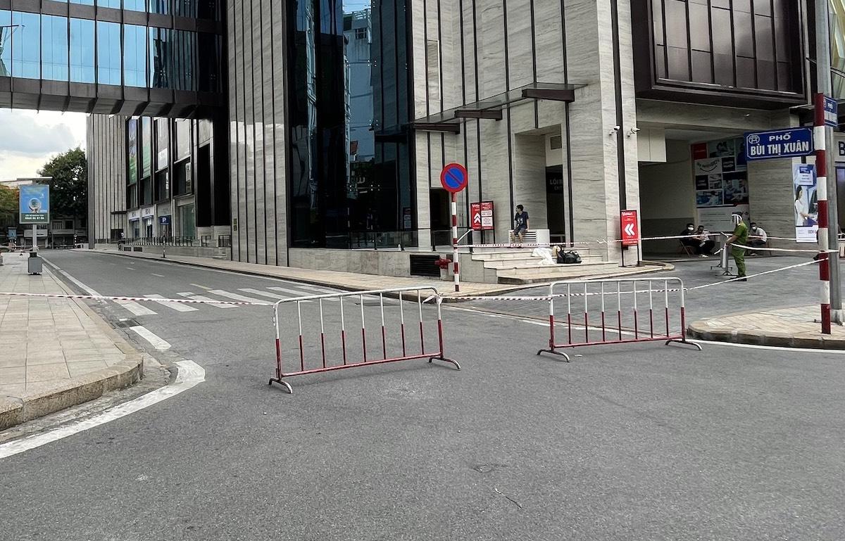 Lực lượng chức năng dựng rào chắn quanh tòa tháp A, trung tâm thương mai Vincom 191 Bà Triệu, chiều 28/7. Ảnh: Giang Huy