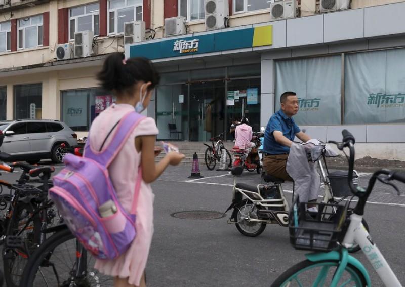Một nữ sinh đứng gần văn phòng cung cấp dịch vụ giáo dục tư nhân ở Bắc Kinh, Trung Quốc, ngày 26/7. Ảnh: Reuter
