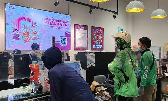Tài xế Grab chờ nhận hàng tại siêu thị Aeon Mall Hà Đông sáng 24/7. Ảnh:Đức Minh