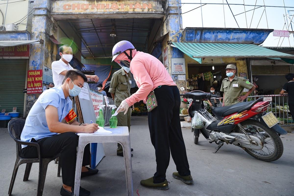 Người dân phường Nhật Tân, quận Tây Hồ dùng phiếu vào chợ mua bán, sáng 27/7. Ảnh: Hà Tùng