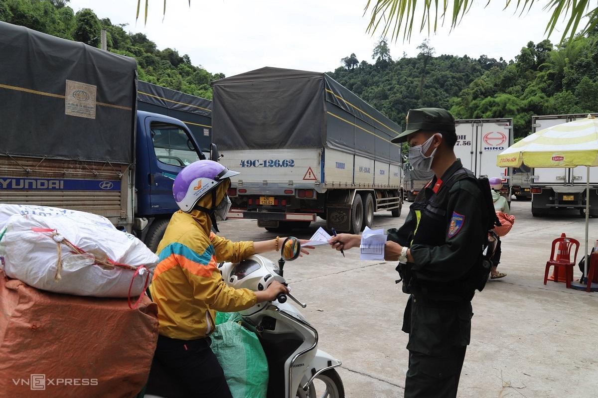 Một người dân đi xe máy về qua chốt kiểm soát Đèo Chuối trên quốc lộ 20. Ảnh: Hoài Thanh