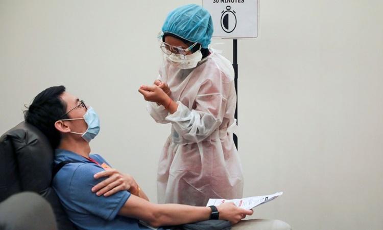Nhân viên y tế nói chuyện với một người vừa tiêm vaccine xong tại Trung tâm Y tế Sunway ở Subang Jaya, Malaysia, ngày 12/3. Ảnh: Reuters.