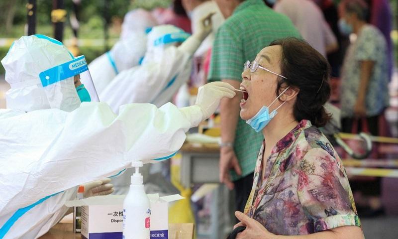 Nhân viên y tế lấy mẫu xét nghiệm Covid-19 cho một phụ nữ ở thành phố Nam Kinh, tỉnh Giang Tô, Trung Quốc hôm 29/7. Ảnh: AFP.