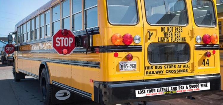 Phía sau một xe buýt chở học sinh còn có rất nhiều cảnh báo: Không vượt khi đèn đỏ sáng, Xe buýt này dừng lại ở mọi điểm giao cắt với đường sắt, và Bạn sẽ mất bằng lái và trả 5.000 USD tiền phạt. Hãy đặt an toàn lên trên hết. Đừng vượt khi đèn đỏ sáng. Ảnh: CFCY