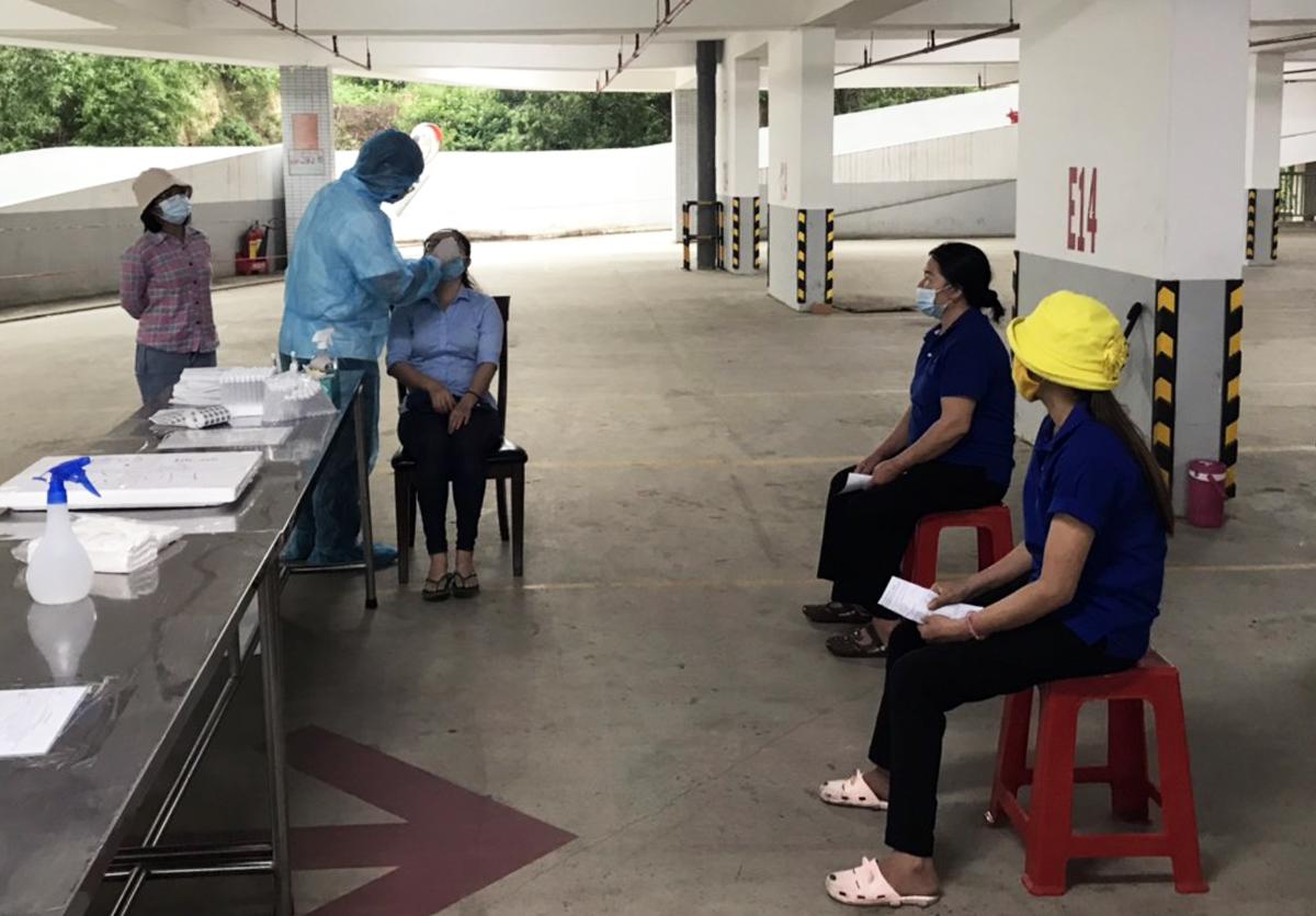 Công nhân nhà máy Timberland chờ lấy mẫu dưới sự điều tiết của nhóm hỗ trợ. Ảnh: An Phương.