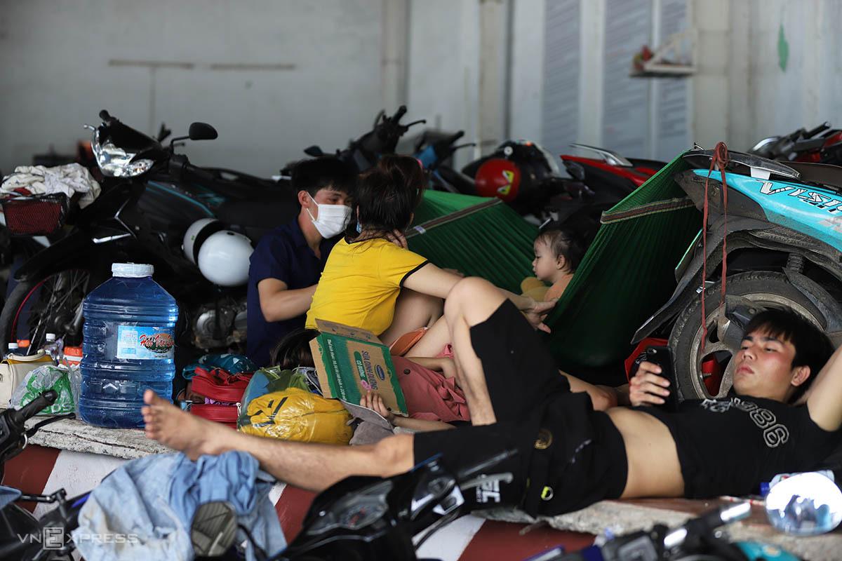 Người dân nằm vạ vật ở chốt kiểm soát thị trấn Lăng Cô chờ xe cách ly tập trung. Ảnh: Võ Thạnh
