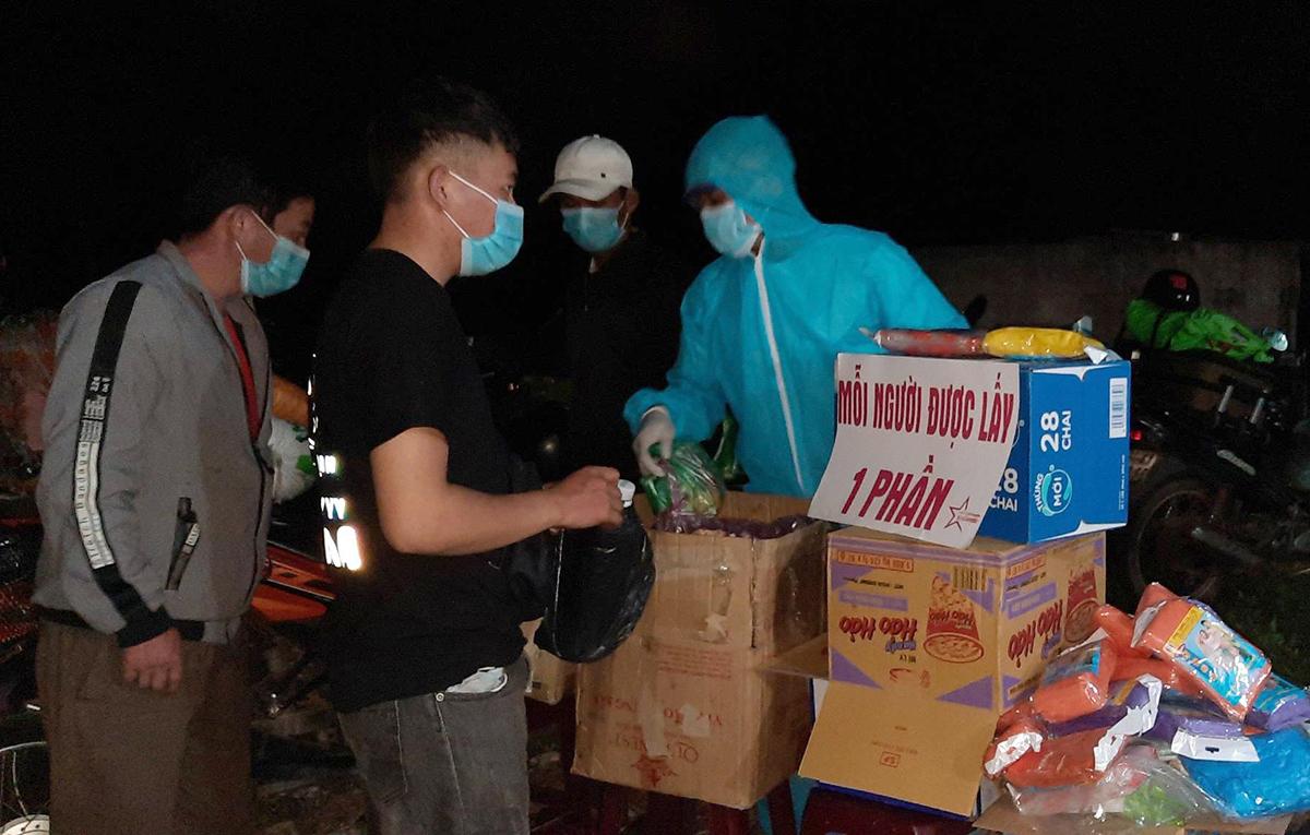 Câu lạc bộ thiện nguyện thị trấn Khâm Đức mang đồ ăn, nước uống đến phục vụ người dân đi xe máy về tránh dịch. Ảnh: Đắc Thành.