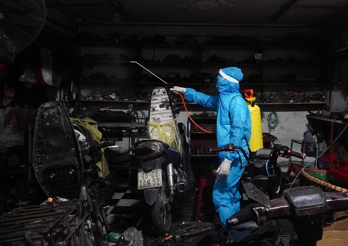 Nhân viên y tế phun khử khuẩn một cửa hàng sửa chữa xe máy ngõ 651 đường Minh Khai tối 1/8. Ảnh: Tất Định.