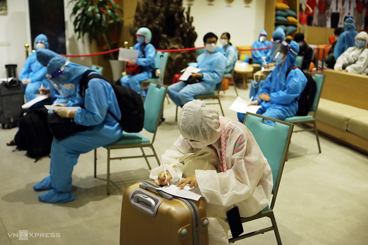 Sinh viên ngồi giãn cách, khai báo y tế trước khi cách ly ba ngày tại khách sạn. Ảnh: Xuân Ngọc.