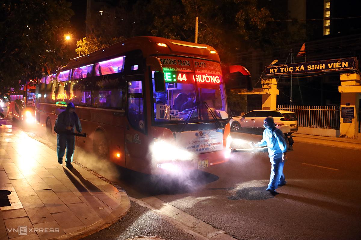 Nhân viên y tế phun khử khuẩn 25 ôtô chở sinh viên từ TP HCM về Khánh Hòa, tối 1/8. Ảnh: Xuân Ngọc.