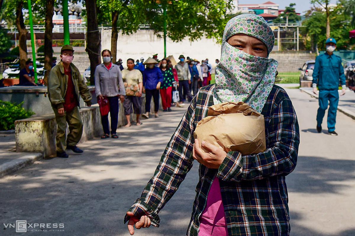 Người nghèo nhận gạo miễn phí tại Nhà văn hoá phường Nghĩa Tân (Cầu Giấy) trong đợt dịch đầu tiên (tháng 4/2020). Ảnh: Giang Huy.