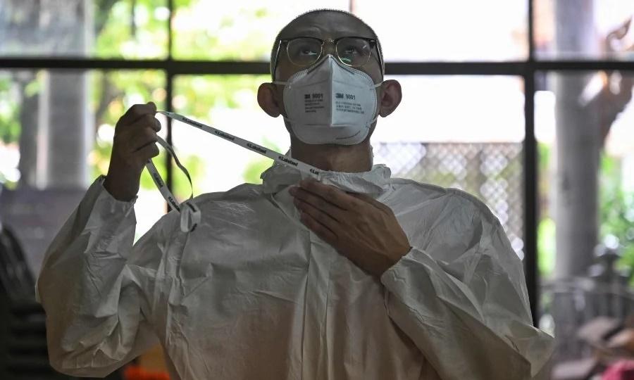 Nhà sư Mahapromphong, phó trụ trì chùa  Suthi Wararam ở Bangkok, mặc đồ bảo hộ trước khi đi lấy mẫu xét nghiệm Covid-19 cho người dân tại khu Charoen Krung ngày 30/7. Ảnh: AFP.