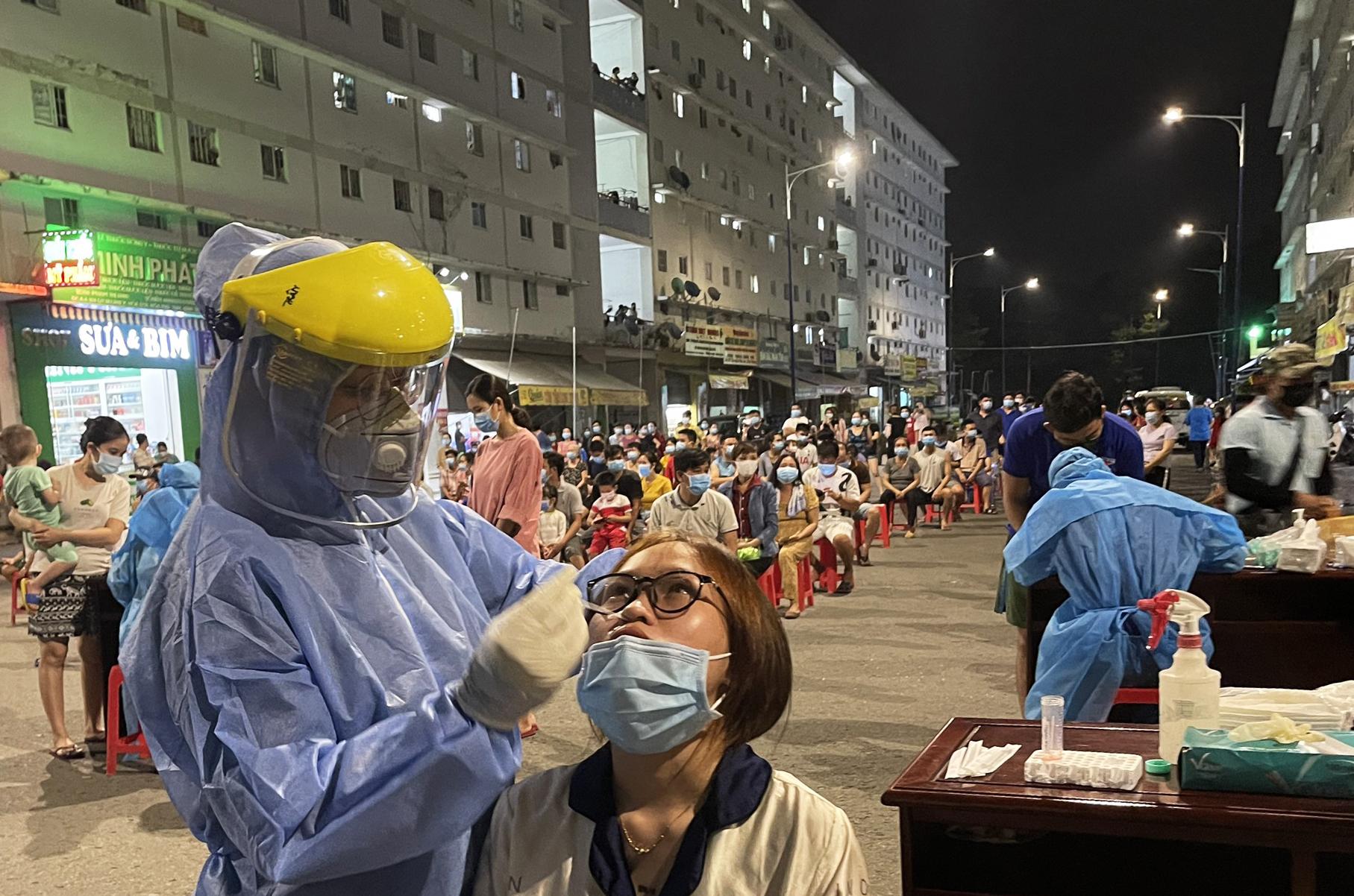 Nhân viên y tế lấy mẫu xét nghiệm một khu nhà ở xã hội tại TP Thủ Dầu Một. Ảnh: Thái Hà