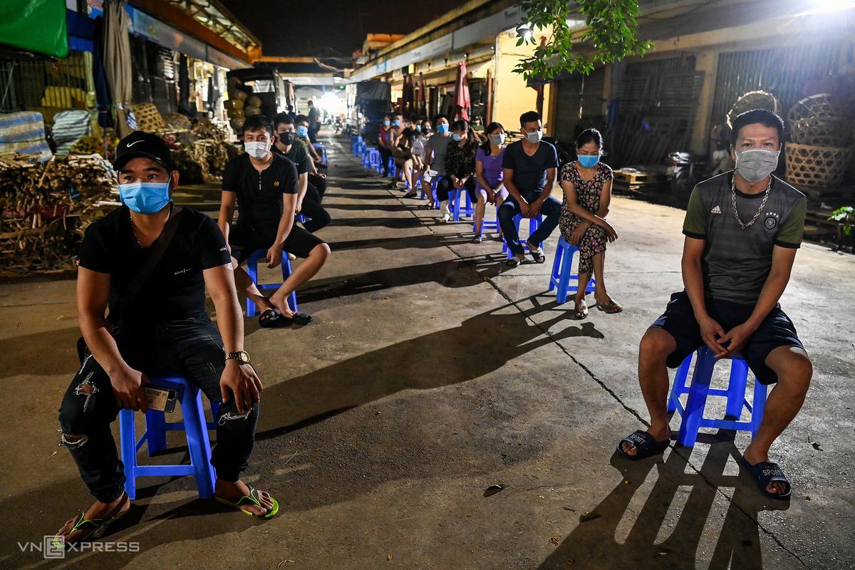 Tiểu thương khu hải sản chợ đầu mối Long Biên chờ lấy mẫu xét nghiệm đêm 1/8. Ảnh: Giang Huy.