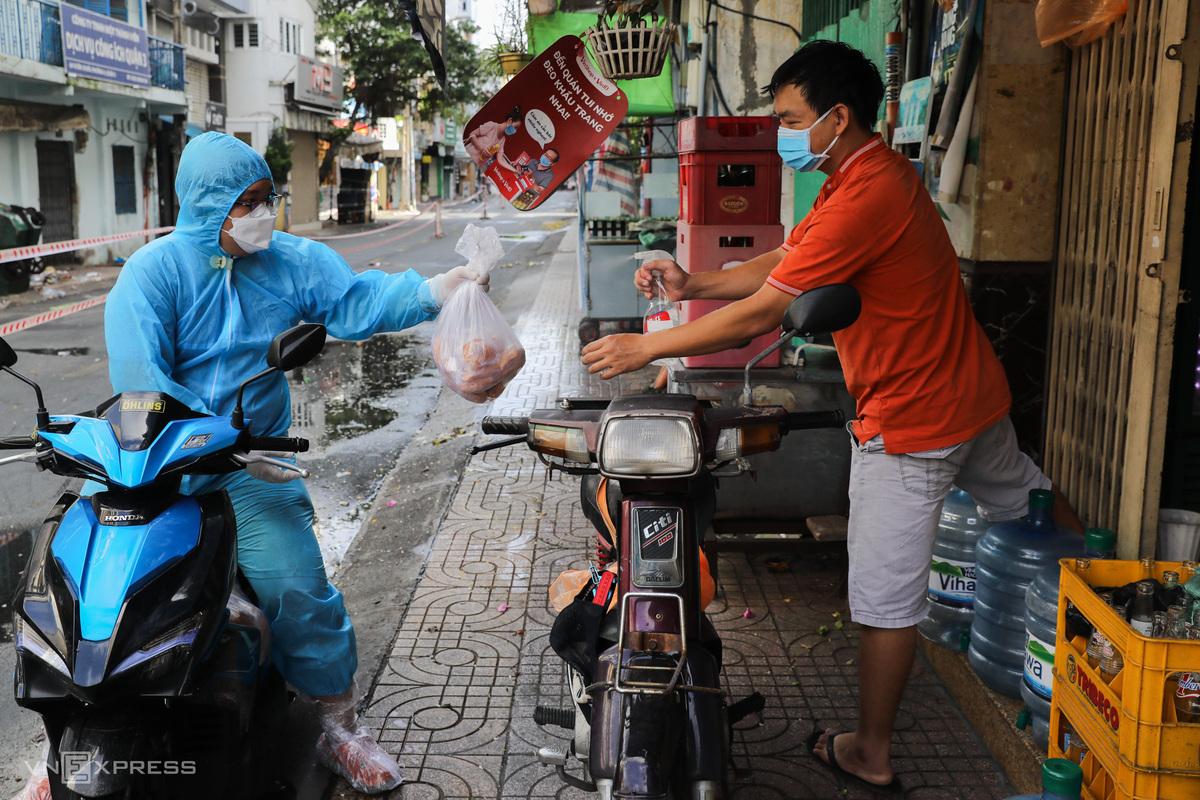 Tình nguyện viên tiếp tế nhu yếu phẩm cho từng nhà trong khu phong toả trên đường Vườn Chuối (quận 3), ngày 30/7. Ảnh: Quỳnh Trần.