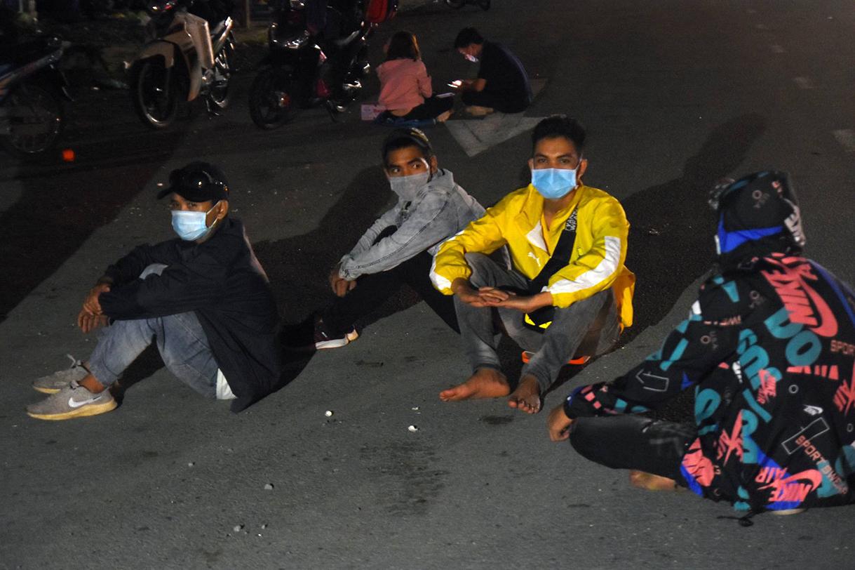 Công nhân ngồi vật vã bên quốc lộ 1K tại chốt kiểm soát TP Dĩ An. Ảnh: Thái Hà