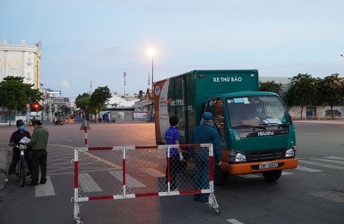 Một xe hoạt động lĩnh vực bưu chính qua chốt kiểm soát đường Phan Văn Trị, quận Gò Vấp, chiều tối 26/7. Ảnh: Gia Minh.