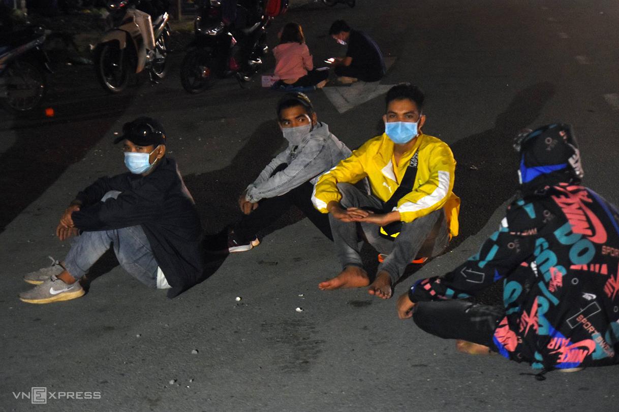 Công nhân ngồi vạ vật gần chốt kiểm soát TP Dĩ An, Bình Dương đêm 1/8. Ảnh: Thái Hà