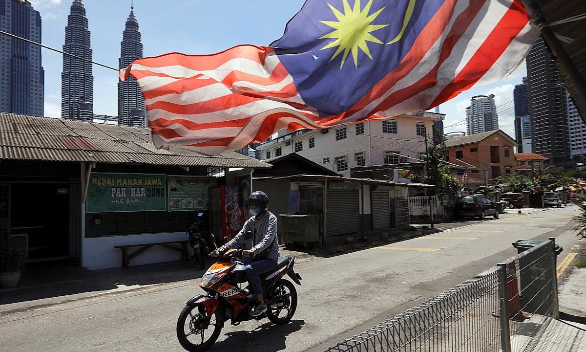 Một người dân đi xe máy trên con phố vắng người ở thủ đô Kuala Lumpur hồi đầu tháng 2. Ảnh: Reuters.