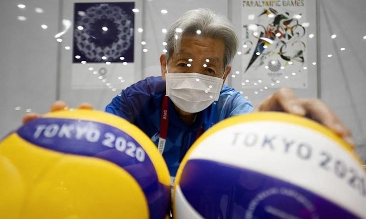 Một tình nguyện viên Olympic Tokyo tạo dáng bên trái bóng chuyền tại trung tâm truyền thống trước khi Thế vận hội khai mạc. Ảnh: AFP.