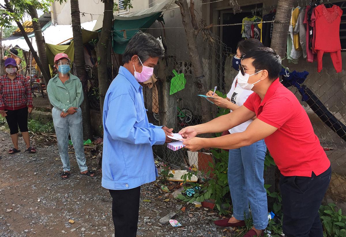 Người dân bị phong toả ở ấp Đông, xã Thới Tam Thôn, huyện Hóc Môn nhận hỗ trợ từ nhà hảo tâm. Ảnh: Lê Tuyết.