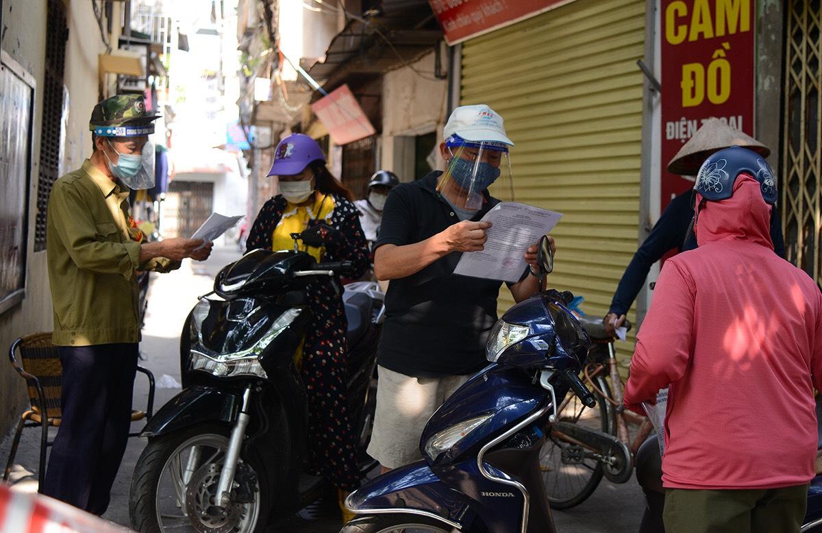 Các tình nguyện viên trực chốt vùng xanh kiểm tra giấy đi đường của người dân khu phố. Ảnh: Tất Định.