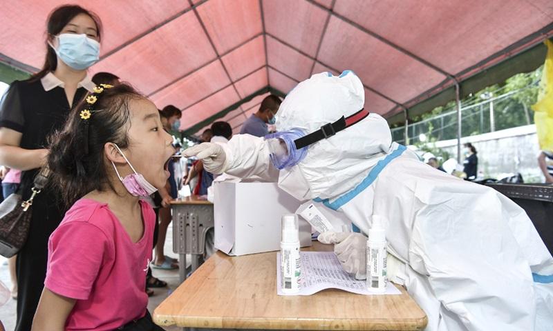 Nhân viên y tế lấy mẫu xét nghiệm Covid-19 cho bé gái ở thành phố Trương Gia Giới, tỉnh Hồ Nam, Trung Quốc hôm 29/7. Ảnh: China Daily.