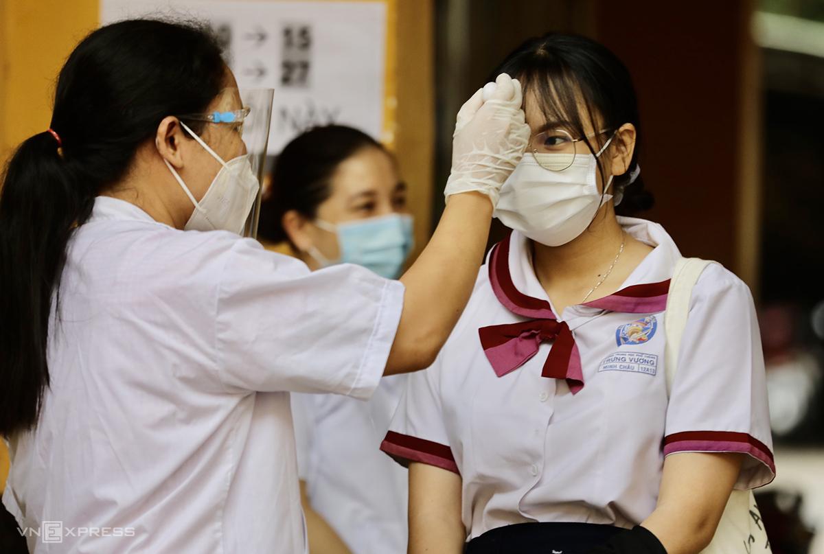 Thí sinh dự thi tốt nghiệp THPT đợt 1 được kiểm tra thân nhiệt trước khi vào điểm thi. Ảnh: Quỳnh Trần.