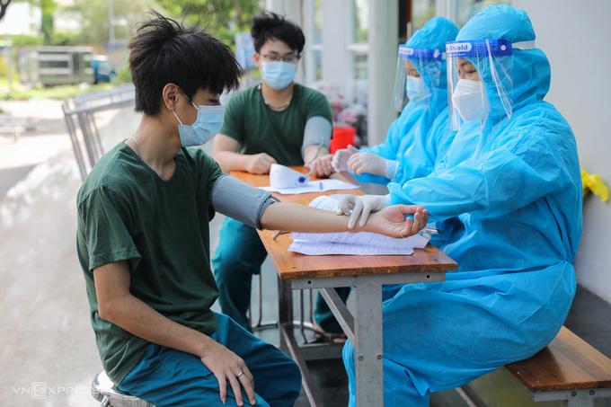 Nhân viên y tế tiêm cho hai dân quân ở khu cách ly trong ký túc xá Đại học Văn Hóa (phường Phước Long A) ngày 1/8. Ảnh: Quỳnh Trần.