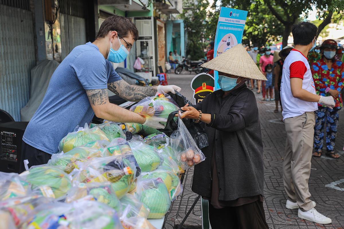 Người gặp khó khăn ở TP HCM nhận lương thực ở một điểm từ thiện, ngày 28/6. Ảnh: Quỳnh Trần.