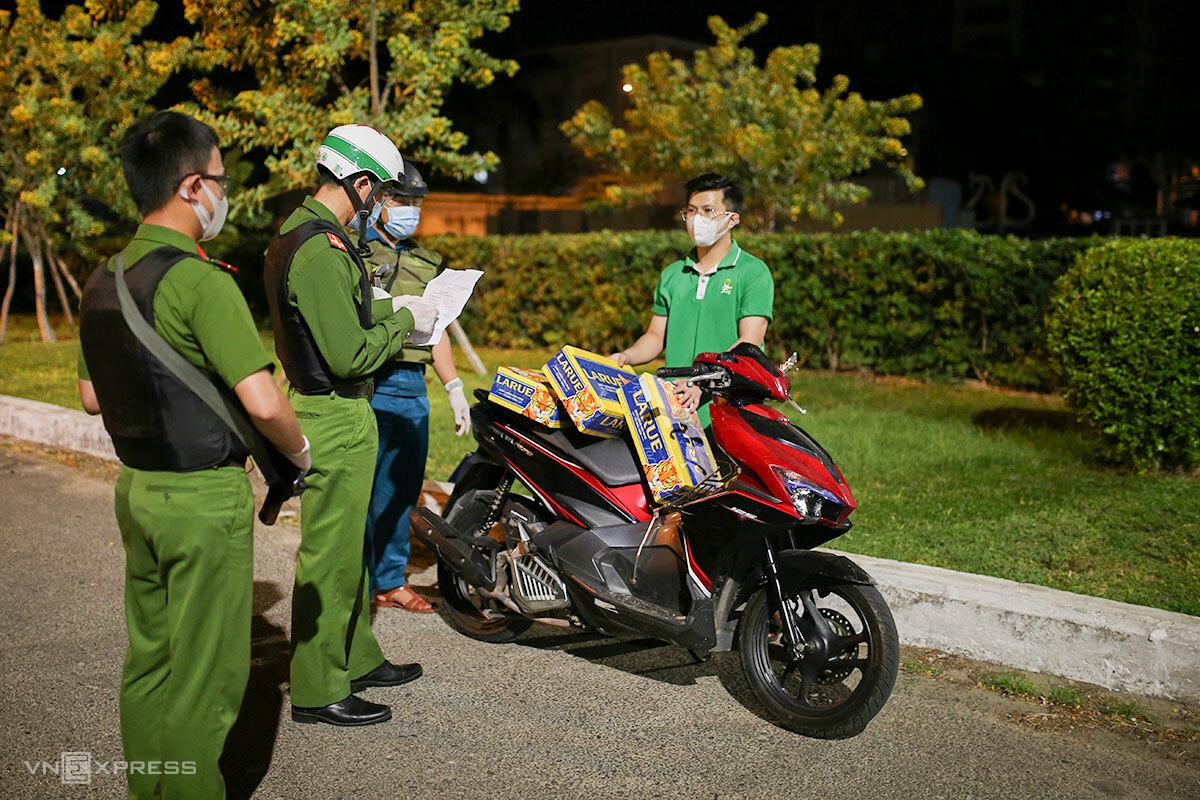 Một thanh niên bị phát hiện chở hàng không thiết yếu, lúc 23h50 ngày 4/8. Ảnh: Nguyễn Đông.