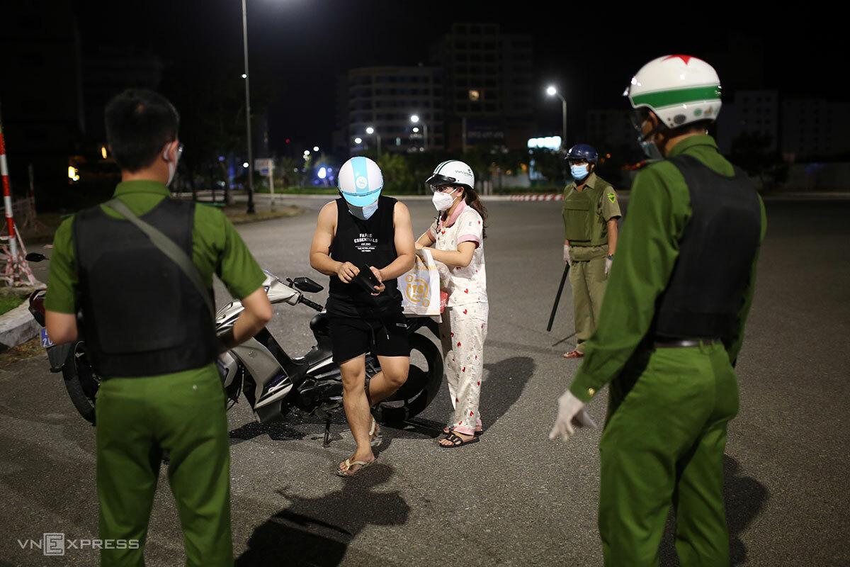 Hai người chở hàng cho khách sạn cách ly bị tổ tuần tra phát hiện dùng giấy đi đường sai quy định. Ảnh: Nguyễn Đông.